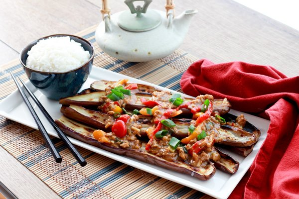 Chinese eggplant on plate topped with garlic sauce and a side of rice