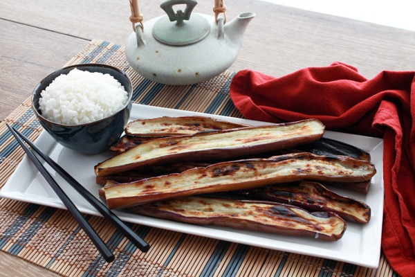 charred Chinese eggplant on plate with white rice and chopsticks