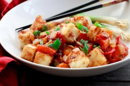 crispy tofu cubes in a sweet and sour sauce in a bowl with chopsticks