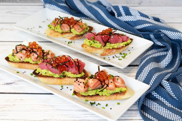 sushi grade salmon and tuna on avocado toast on white plates