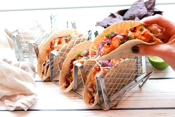bang bang shrimp tacos in a taco holder and a taco held by hand
