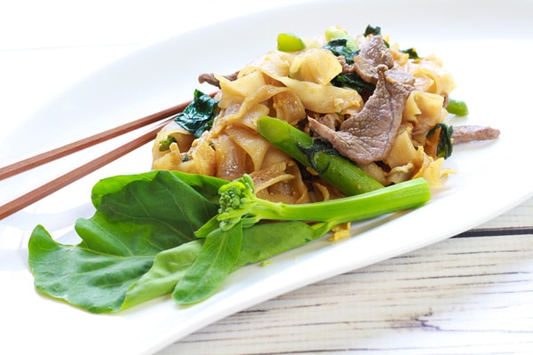 Thai Pad See Ew stir fried noodles on a plate with chopsticks and Chinese broccoli