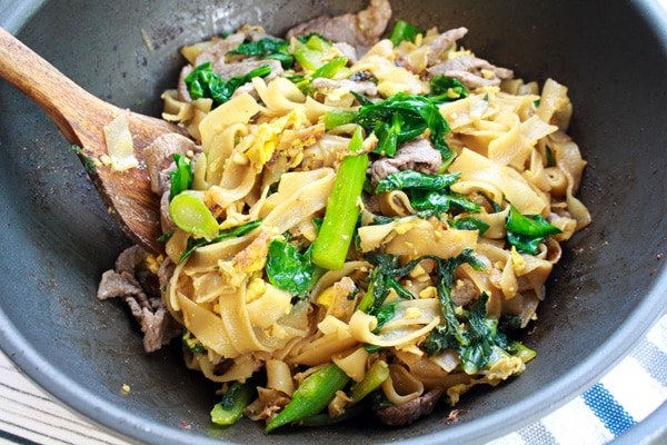 Thai Pad See Ew stir fried noodles in a wok with a wooden spatula