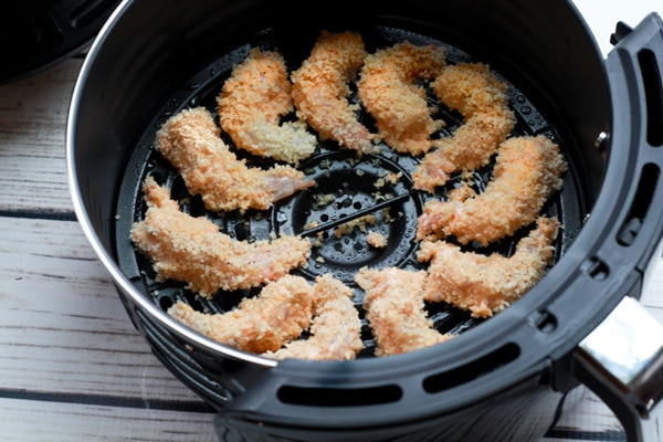 breaded shrimp in an air fryer basket