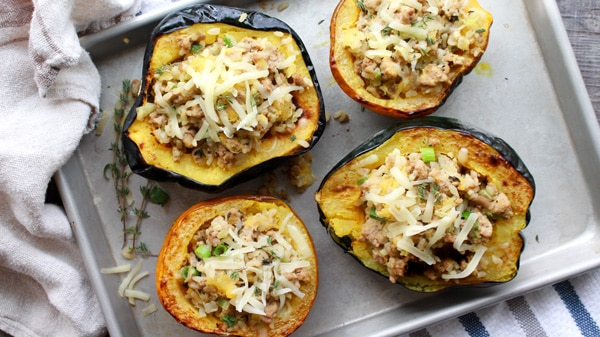 stuffed roasted acorn squash with ground turkey and rice on a baking tray