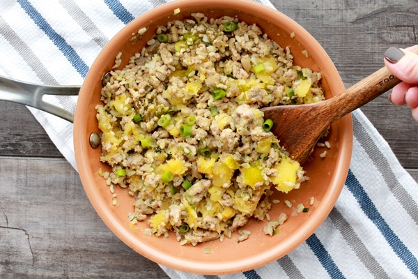 acorn squash stuffing with turkey and rice in a saute pan