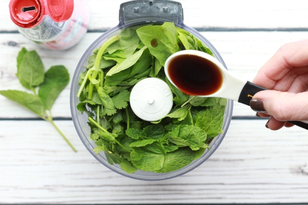 fresh green herbs in a food processor with a fish sauce pour