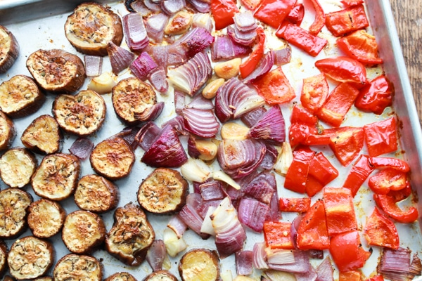 roasted sliced eggplant, red onions, and red peppers on a baking sheet