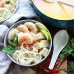 Singapore laksa with shrimp, tofu, and rice noodles in a bowl and in a Dutch oven with ladel