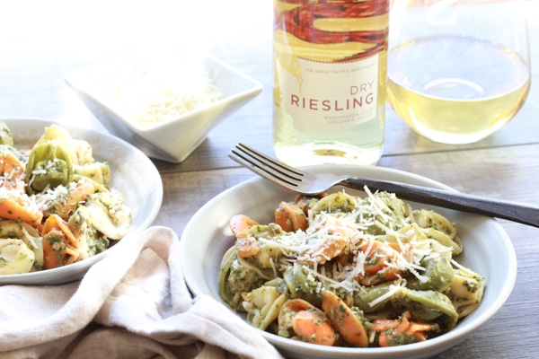 Tri-color tortellini in a bowl with Thai pesto sauce and bottle of Riesling wine