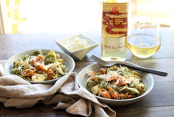 Tri-color tortellini in a bowl with Thai pesto sauce and a bottle Riesling wine