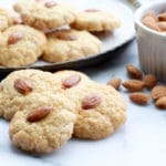 Chinese almond cookies on a plate with almonds