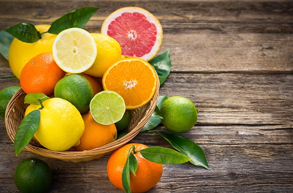 fresh and juicy citrus fruits in a basket on the rustic wooden table