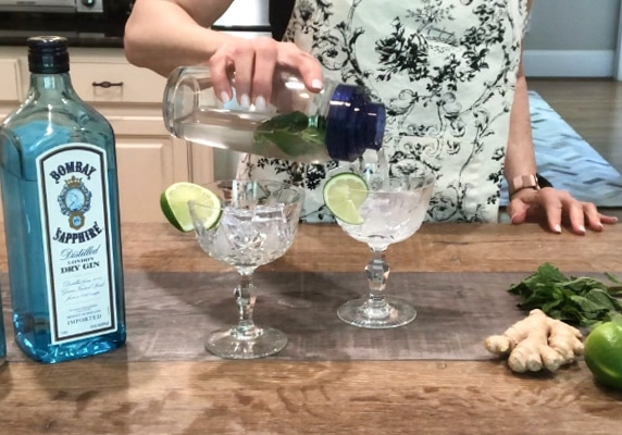 Pouring minty gin fizz cocktail into a crystal glass with Bombay gin on the side