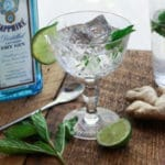 minty gin fizz cocktail in a crystal glass with a lime slice and bottle of Sapphire gin