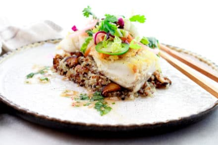 pan seared halibut on top of a bed of quinoa and topped with a spicy nuoc cham slaw