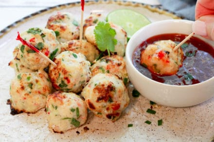 spicy baked shrimp balls on a plate being dipped in a sweet chili sauce
