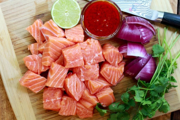 cubed raw salmon on a cutting board with lime, sauce, red onions, and cilantro sprigs