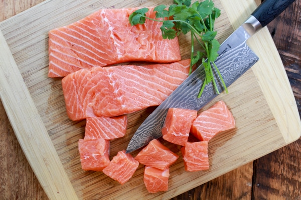 raw salmon on cutting board with chef's knife and cilantro sprigs
