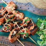 red curry salmon kebabs on skewers with a drizzle of aioli sauce