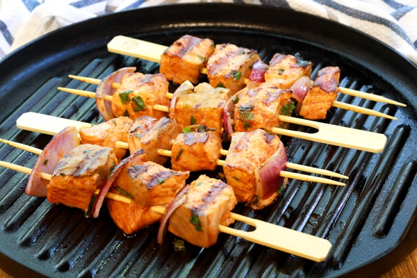 red curry salmon kebabs on skewers on a grill pan