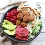 falafel balls in a bowl with beet hummus, slaw, red onions, and avocado on a white board and fork