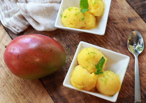 mango coconut sorbet in white bowls with a whole mango on the side