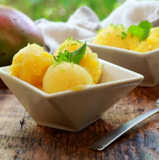 mango coconut sorbet in white bowls with a spoon and whole mango in the background