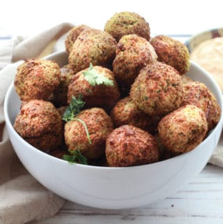 air-fried falafel balls in a white bowl with a side of spicy aioli dipping sauce