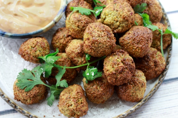 air-fried falafel balls on a plate with a side of aioli dipping sauce