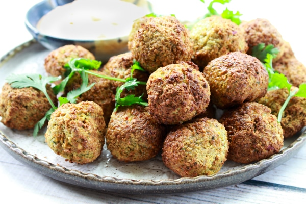 air-fried falafel balls on a plate with a side of spicy aioli dipping sauce