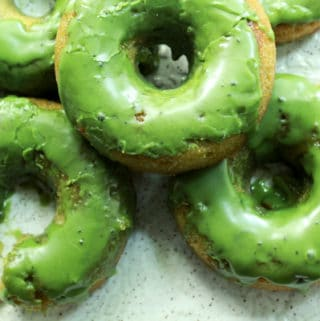 matcha donuts stacked on a white plate