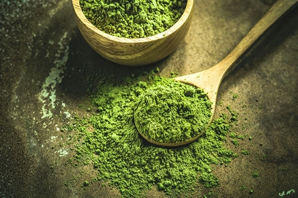 matcha powder in a wooden bowl and wooden spoon
