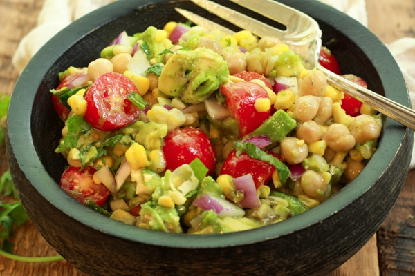 a vibrant corn and avocado salad in a black wooden bowl with a large silver fork