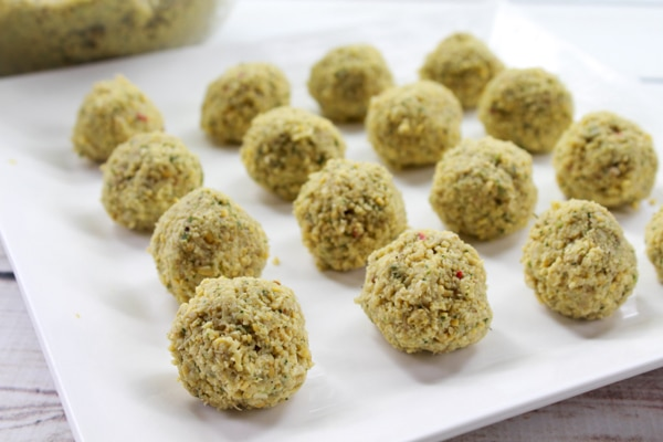 Uncooked falafel balls on a white plate