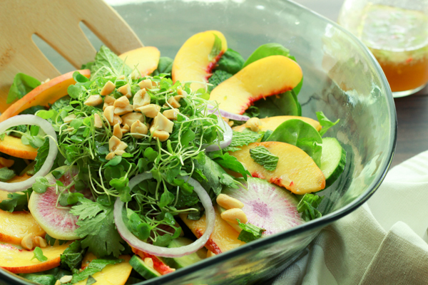 Asian peach salad with fresh herbs on a bed of spinach in a glass salad bowl