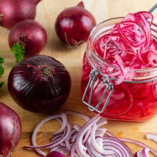 homemade pickled sliced red onion in a mason jar and raw on a board