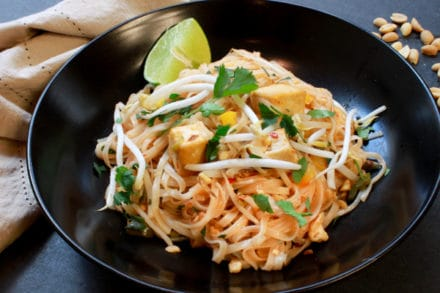 tofu pad thai garnished with a lime wedge in a black bowl