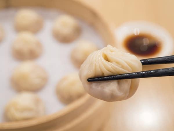 Closeup of Xiao Long Bao with chopsticks, Steamed Pork Dumplings, Taiwan food