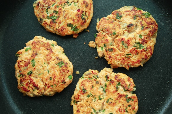 wild salmon burgers browning in a pan