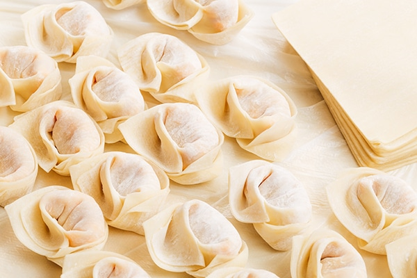 uncooked homemade Chinese dumplings with wrappers