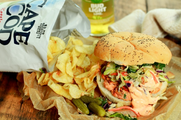 wild salmon burger topped with broccoli slaw and a spicy aioli, with a side of chips
