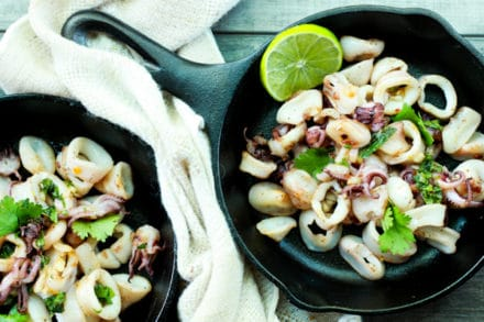 seared calamari in two cast iron pans with a slice of lime