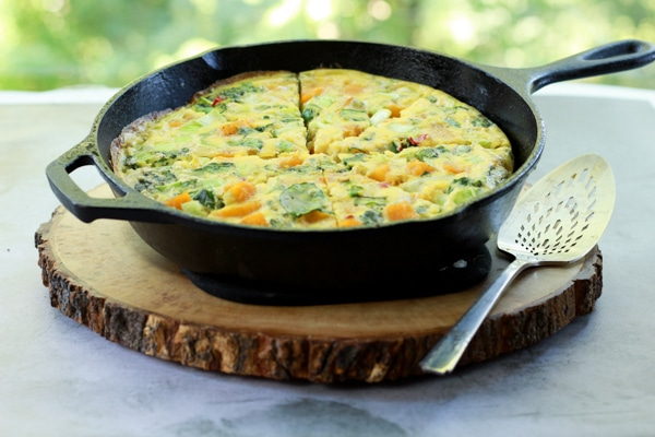 a roasted butternut squash and baby bok choy frittata in a cast iron pan on a round wooden board with a silver serving piece