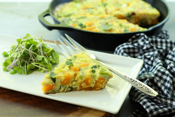 a slice of roasted butternut squash and baby bok choy frittata on a white plate with a silver fork and checkered napkin