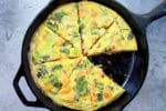 a roasted butternut squash and baby bok choy frittata in a cast iron pan on a gray board