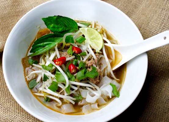 Vietnamese chicken noodle soup in a white bowl with garnishes of fresh Thai basil, hot chili peppers and lime.