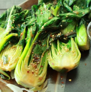 baby bok choy on a plate with a side of red pepper flakes