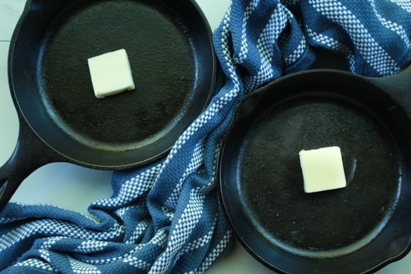 pats of butter in mini cast iron skillets on a blue napkin