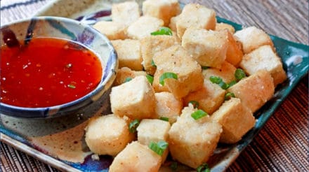 crispy tofu cubes on a plate with a side of sweet chili dipping sauce